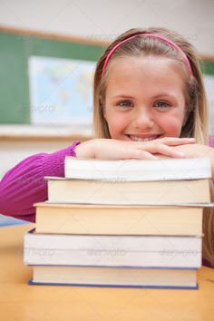 Portrait of a smiling schoolgirl posing with a stack of books ...  One Person, adorable, background, blackboard, board, book, caucasian, cheerful, child, childhood, class, classroom, cute, desk, education, educational, elementary, girl, happiness, happy, indoors, knowledge, laying, leaning, learn, learning, lifestyle, looking, pile, posing, pretty, primary, relax, school, schoolchild, schoolgirl, sitting, smile, smiling, stack, student, study, studying, success, table, textbooks