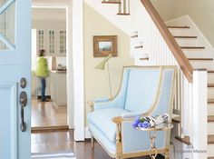 A classic robin's egg blue settee offers a pretty perch to put on shoes, and picks up on the blue front door. | Door colour, Exhale (AF-515) in Semi-Gloss, Benjamin Moore Aura Exterior; entryway wall colour, Jute (AF-80) in Eggshell, Benjamin Moore Aura. | #paint #decor