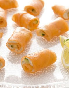 Smoked Salmon Rolls  12 oz smoked salmon slices   grated zest of 1/2 lemon   1 cucumber   1 tsp chopped dill   4 oz (110 g) cream cheese, softened  1 tsp prepared horseradish   2 tbsp mayonnaise   dill sprigs and lemon wedges to serve