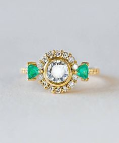 With the lowest of profiles, this fantastically sparkly ring is perfectly comfortable for everyday wear. Rich 18k yellow recycled gold gives the diamonds a warm brilliance that helps them shine just a little bit brighter. Elegant and unique trillion cut Emeralds from the Nova Mine in Brazil and a center bezel add a new world modern touch to this classic post-consumer vintage Diamond minimal engagement ring.