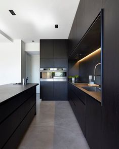 kitchen idea - M House is a minimalist house located in Melbourne, Australia, designed by DKO. The kitchen space features blacked out custom cabinetry with a black kitchen island that allows for seating and serving. Modern Kitchen Cabinets, New Kitchen, Kitchen Dining, Kitchen Ideas, Kitchen Modern, Awesome Kitchen, Kitchen Layout, Kitchen Contemporary, Modern Kitchen Lighting