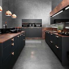 Modern industrial style kitchen with concrete floors and copper pendant lights