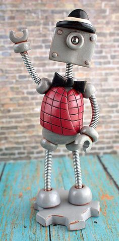 Custom robot sculpture I created in November 2013, a gift from mother to son based off the illustrations of the gentleman in the photo. 'The Two Story House' robot was a delight to create. Vest, hat and single cute eye. Handmade by HerArtSheLoves.
