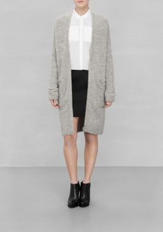 A lengthy cardigan made from a fuzzy warmth-bringing fabric, featuring an edgy zip-closure.