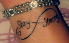 "Little wrist tattoo of the infinity symbol saying ""Stay strong"" with a heart inside, on Tanicha."