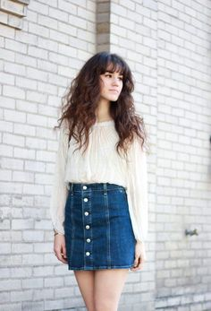 A billowy, ladylike blouse looks effortless paired with a denim mini skirt. Tonya of The Mop Top nails the look in a button-front skirt. This outfit will work with gladiator sandals and into fall with knee-high boots.