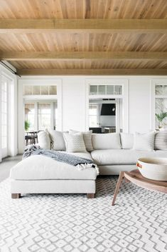 White living room with light grey sectional and modern wood coffee table with wood paneled ceiling and beams | Cortney Bishop