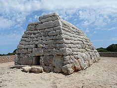 La Naveta Des Tudons es el monumento prehistórico más famoso de Menorca y de las islas Baleares . Cuenta la leyenda que es el edificio más antiguo de toda Europa. Las navetas son construcciones propias de Menorca y son de los monumentos funerarios más antiguos que se pueden saber. Se construyeron sobre el año 1000 a.C. y pertenecen a la cultura talayótica de la isla. En su construcción no se utilizó ningún tipo de cemento y son tan sólo piedras encajadas.