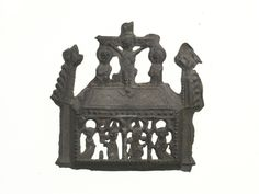 Pilgrim badge in the shape of a gabled reliquary (container for a saint's relics) from the shrine of St Thomas Becket at Canterbury Cathedral. The figures of Christ on the cross, the Virgin Mary and St John stand on the roof. Below the roof are four arches, each with a standing figure inside. The second figure from the left is holding a cross-staff and may be St Thomas Becket. Production Date: Late Medieval; early-mid 15th century