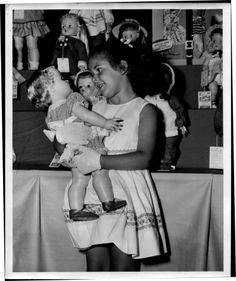 Love at first sight...little girl holding doll, 1961.