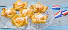 Lekkere oranje bladerdeeg gebakjes met custard en abrikoosjes in de vorm van een kroontje