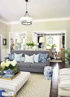 Elegant, open concept living room, with with grey sofas and drum shade pendant lights create a neutral backdrop of layers of beautiful blue patterned pillows and blue and white pottery and garden stools. Decorated for Summer with fresh cut greenery, hydra