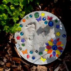 DIY stepping stone: 1 bag of stepping stone mix from craft store, 1 plastic mold from craft store (shapes vary) OR a plastic pot holder from dollar store if you want a round stone, colored rocks from dollar store (craft store has more variation in color but outrageous prices) and then you can add mosaic tile pieces, tiny mirrors or other tile shapes like butterflies, flowers & leaves :) Add a footprint, handprint, dates and names! Paint if desired.