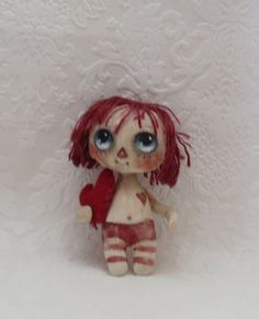 Tiny Raggedy Anne cloth doll with red heart
