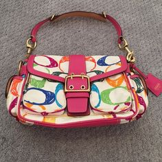 CLOSET CLEARANCE Multi colored coach handbag Multi colored coach handbag with a front flap and two zippered front pockets along with two side flap pockets. Rare style. Barely used. One tiny stain on front that can probably be washed off. Inside of purse perfect condtion. Paid alot for this purse Coach Bags