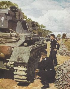 Panzer IV color photo. There is an open tool box on top of the turret stowage bin, and a tarp laying on the turret roof by the commanders cupola. The crew, wearing the black uniform with pink piping on the collars, standard issue to tank crews, are inspecting the tracks for wear and also resetting track pins as evidenced by the hammer in the hand of the crouching crewman.