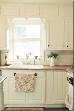 I like the cabinets and butcher block counters, but I love the dish towel rack in front of the sink!
