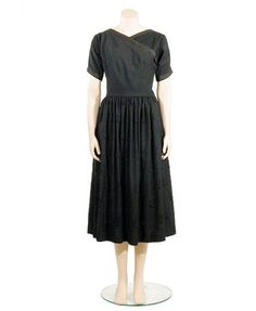 Clare McCardell Embroidered Black Wool Dress  American, 1950s  Crisscross bias bodice with V-neck, elbow length sleeves, wool tape edging neck and sleeves, full gathered skirt embroidered overall with fringed circular motifs in black cotton floss.