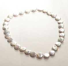 FRESHWATER PEARL COIN NECKLACE - Cultured pearls that complement any outfit. 17-inch necklace with 13-mm freshwater coin pearls and sterling silver.    Naturally white cultured pearls that complement any outfit.    Includes a beautiful jewelry bag. $66.