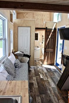 The interior features linoleum wood grain flooring throughout the main level and wainscoting on the walls.