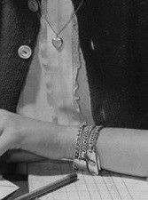 The trendy thing was to wear multiple identification bracelets with yours, your friends, or boyfriend's names.  A necklace chain with a ring, locket or hobby piece (football, tennis) hanging from it was worn over blouses and sweaters.
