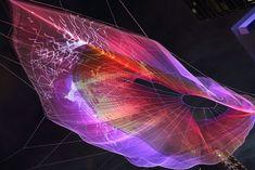 """""""Unnumbered spark"""", Janet Echelman and Aaron Koblin. Escultura aérea, cuyos  patrones de color son diseñados por los espectadores desde sus celulares mediante una interfaz web. La estructura de cables de polímero se convierte en un lienzo gigante suspendido en  el cielo que cobra vida con la interacción de cada transeúnte, estimulado a detener el paso, cambiar la perspectiva de su mirada, vincularse al compartir su asombro y convertirse en co-creador de una obra que hipnotiza. (Clik → site)"""