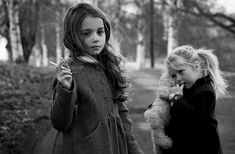 Dianne takes a picture of two little girls who are smoking cigarettes. They are way too young for that...