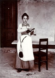 Ganzporträt einer Serviererin mit umgehängter Geldtasche ein Bier einschenkend. o.J. um 1900  G[ustav] A. PEYRL junior, Herzogenburg, N[ieder-]Oest[erreich].