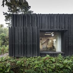 House in Normandy, France by Marchi ArchitectesAn extension with dark timber cladding that plays with light and shadows disappearing into the shade of the surrounding forest.
