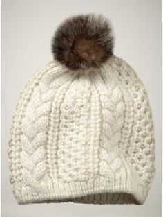 Cabled Pom Pom Hat from Gap $30 Knitting inspiration: Varying cable patterned panels around a light neutral hat in a worsted weight yarn with fur Pom Pom.
