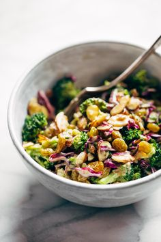 Broccoli Salad with creamy almond dressing - non-mayo-based vegan goodness! with purple cabbage, raisins, almonds, green onions, and almond butter dressing.