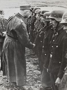 "SS-Oberführer Max Simon, wearing the rubberized motorcycle coat, presents the Iron Cross Second Class to the brave soldiers of the Division ""Totenkopf"" which had been encircled for several months in the Demyansk Pocket in the winter of 1941-42. Note the officer standing behind is wearing a variation of the uniform seen in this division - Totenkopf emblems on both collar patches."