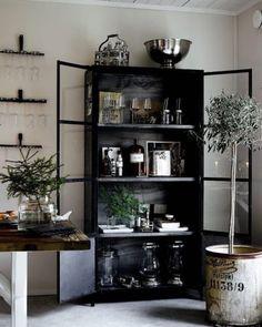 Upea musta vitriinikaappi hallitsee kauniisti tilan tyyliä ja tunnelmaa, tarjoten samalla mukavasti säilytystilaa.