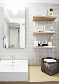 Keskikerroksen kylpyhuoneeseen Madeleine valitsi Indan H2O-sarjan kalusteet, lavuaarin ja peilin. Pienet, harmaat mosaiikkilaatat ovat ranskalaista hiekkakiveä. Woodnotesin koriin on taiteltu pieniä pyyhkeitä.