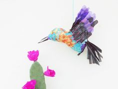 """Le printemps rime avec couleurs, fleurs, parfums et la douce mélodie des oiseaux le matin.  Pour le défis OuiAreMakers """"vive le printemps"""", j'ai choisi de réaliser un petit colibri multicolore en papier mâché.  J'adore ces petits oiseaux aux couleurs métalliques qui sont toujours entrain de bouger.  J'espère qu'il vous plaira et qu' il s'invitera dans votre déco de printemps !"""
