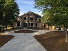 DH Custom Home, custom Pendleton in Chesterfield, MO. This home was build in the Forest Hills Country Club neighborhood. We were inspired to design a driveway in the shape of a golfball on a golf tee. Unique and fun, we loved this addition to the home! #driveway #customhome