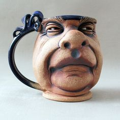 Each mug is created from a ball of stoneware clay and begun on the potters wheel. The moist mug is then pushed, poked, and added to creating a one of