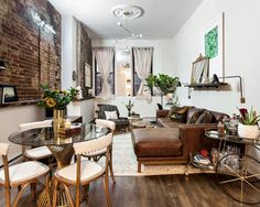 This elegant, eclectic studio makes the most of its space. In the far corner, a home office sits with a modern desk and rolling chair. Behind that, a sitting area gives the tenant a place to entertain, while the living room, sandwiched in the middle of the space has a large leather sofa with a chaise lounge to maximize seating potential. A breakfast cart and small table provide a place for the tenant to enjoy her meals.