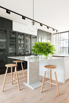 """The breakfast bar is an example of how the room-within-a-room scenario allowed us to layer the kitchen in a way not previously possible,"""" says design director Paul Hecker, who sectioned off the south end of the kitchen with a glazed window screen to facilitate a multipurpose breakfast bar by day and cocktail bar at night."""