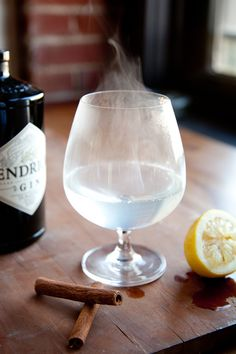 A hot toddy made with gin, sugar and lemon juice, garnished with cinnamon sticks