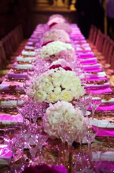 Beautiful white and red floral arrangements accentuate bold pink menus placed at guest's seats.