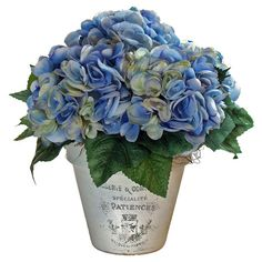 Artful on its own or anchoring an organic-chic vignette, this faux hydrangea arrangement is nestled in a ceramic pot adorned with French typography.