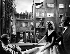 "James Stewart, Grace Kelly and Alfred Hitchcock on the set of ""REAR WINDOW"" (1954)."