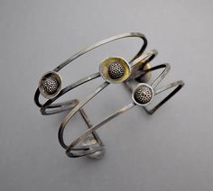 A sterling silver cuff with an open strappy design with neat berry cup elements. Unique and great on the wrist, Will fit small to medium wrist sizes. 1- 1/4 in width.