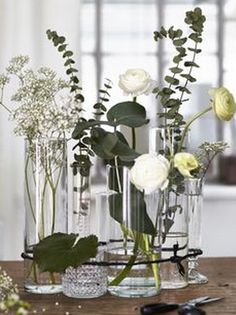 For a modern twist on the traditional flower arrangement, group a variety of clear glass vases with randomly placed flowers together and bind with twine. Ikea hack