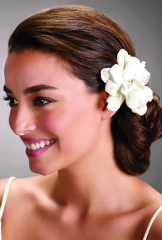A low figure-eight chignon, accessorized with a fresh gardenia. Photo by Alex Beauchesne for BRIDES