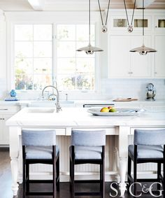 Kitchen with white walls, large windows, white cabinets, white counters, white tile backsplash, wood floors, light blue barstools, and silver light fixtures