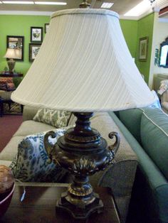 This beautiful aged brass table lamp has a  trophy like appearance, that paired with a beige lined shade, modernizes it's antique appearance