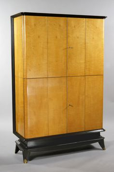 "Art Deco Cabinet Maurice Jallot (1900-1971) France, ca. 1940 Sycamore and stained fruitwood. Four-door cabinet with one wide shelf in each section and a pull-out tablet at the midpoint, hidden by the closed doors. Cabinet raised on a stained plinth with brass sabots. Height: 66.75"" Width: 44"" Depth: 17"""