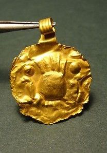 1st Millennium BC. Gold round sheet pendant with a ritual image of an altar in the center with lit ceremonial fire and two figures on the sides.
